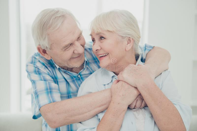 Foto av två nätta åldriga folkpar som framlänges kramar bekväma känslor för ridtur på axlarnafamiljstående inomhus royaltyfri foto