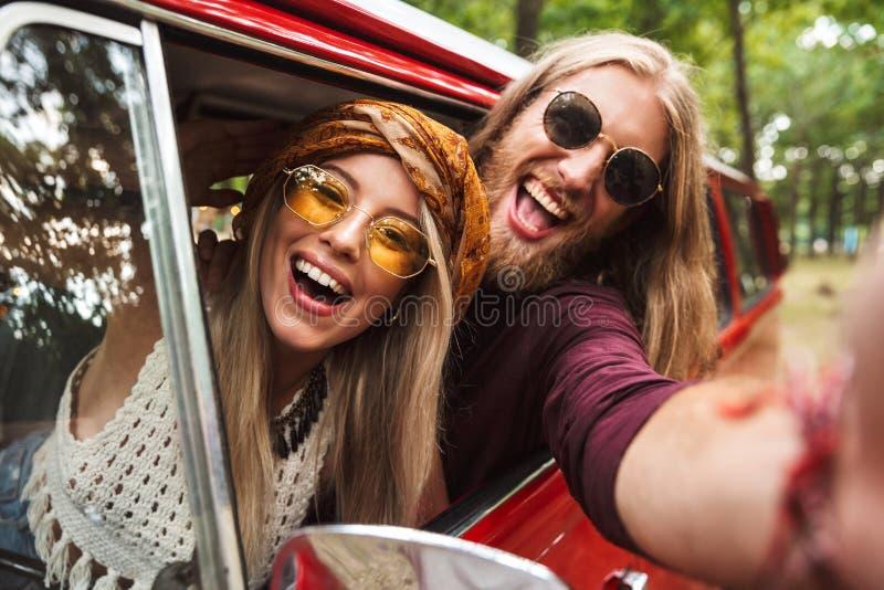 Foto av unga hipsters man och kvinna som ler och sitter i beträffande royaltyfri bild