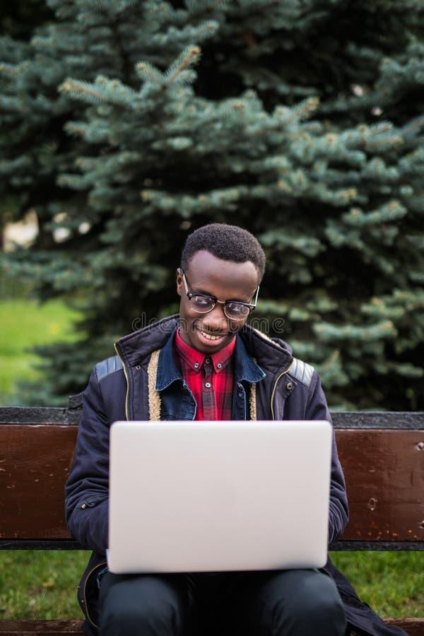 Foto av ungt afrikanskt gladlynt mansammanträde på bänk och användabärbara datorn se kameran royaltyfria bilder