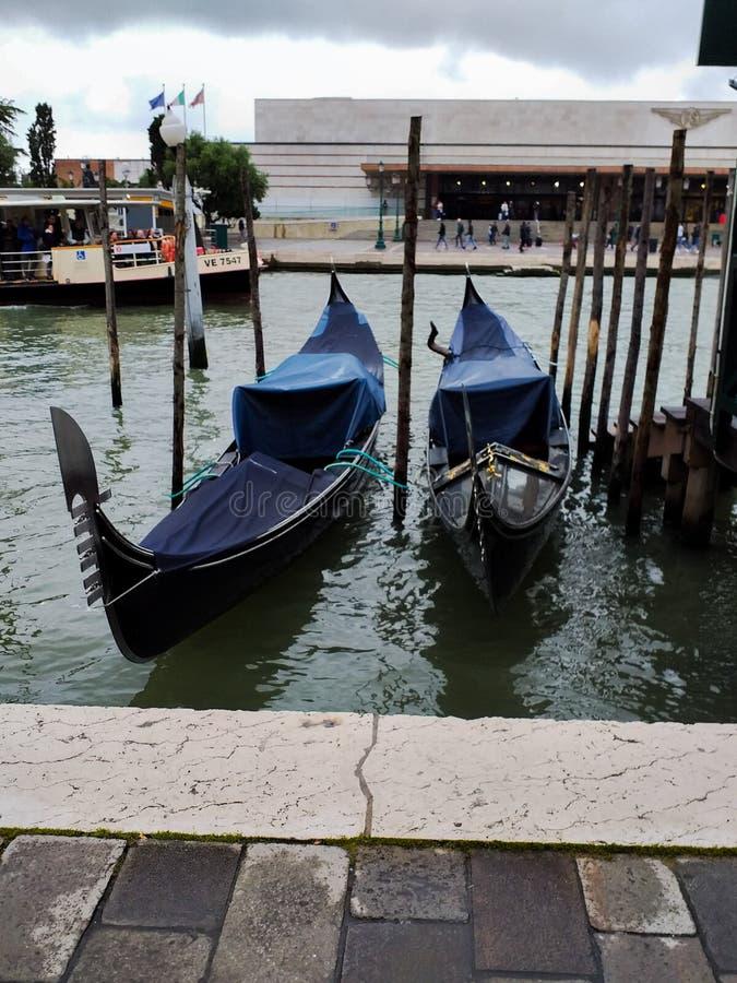 Foto av Venedig nära stationen f?rt?jde gondoler typisk Venetian fartyg arkivfoto