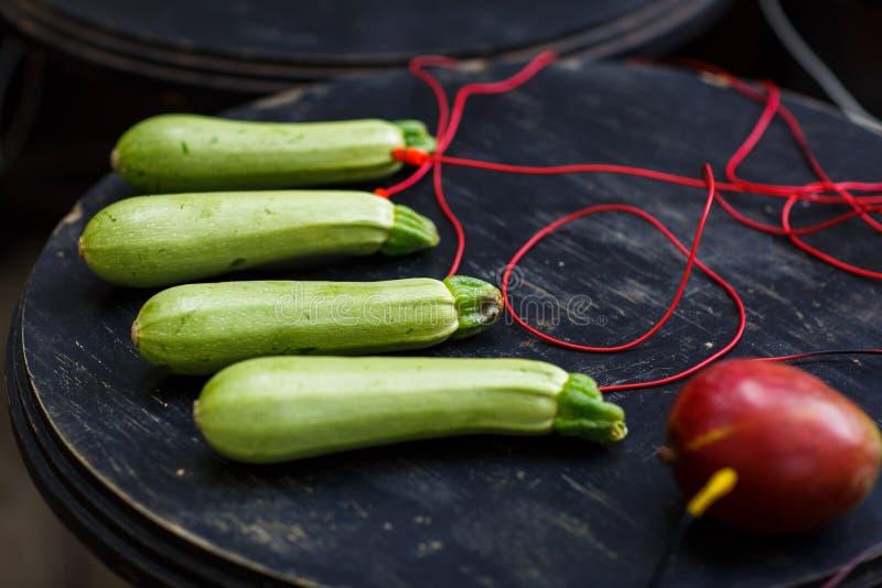 Foto av zucchinin, avokado med röda trådar på den svarta tabellen arkivfoton