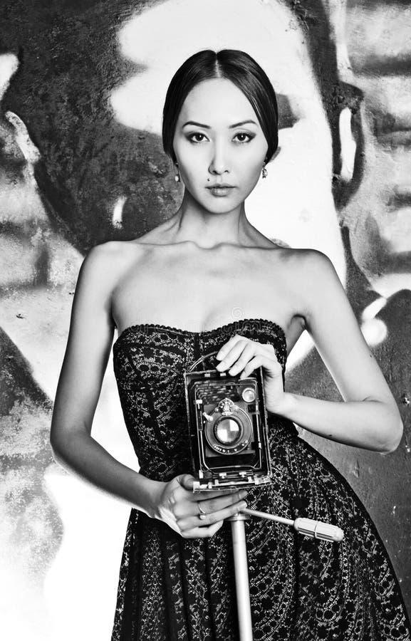 Foto Aziatische vrouw in kleding met naakte schouders en oude camera stock foto