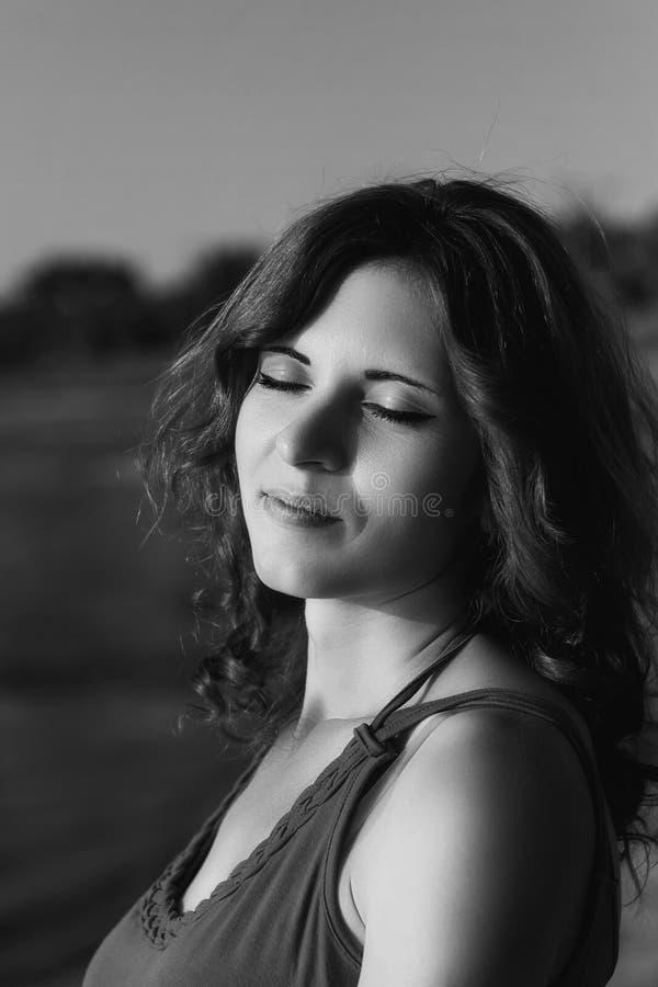 Foto in bianco e nero al tramonto di bella ragazza con la h riccia immagine stock