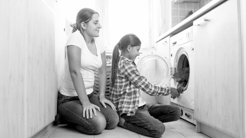 Foto in bianco e nero della madre con la figlia che fa lavoro domestico alla lavanderia fotografia stock libera da diritti