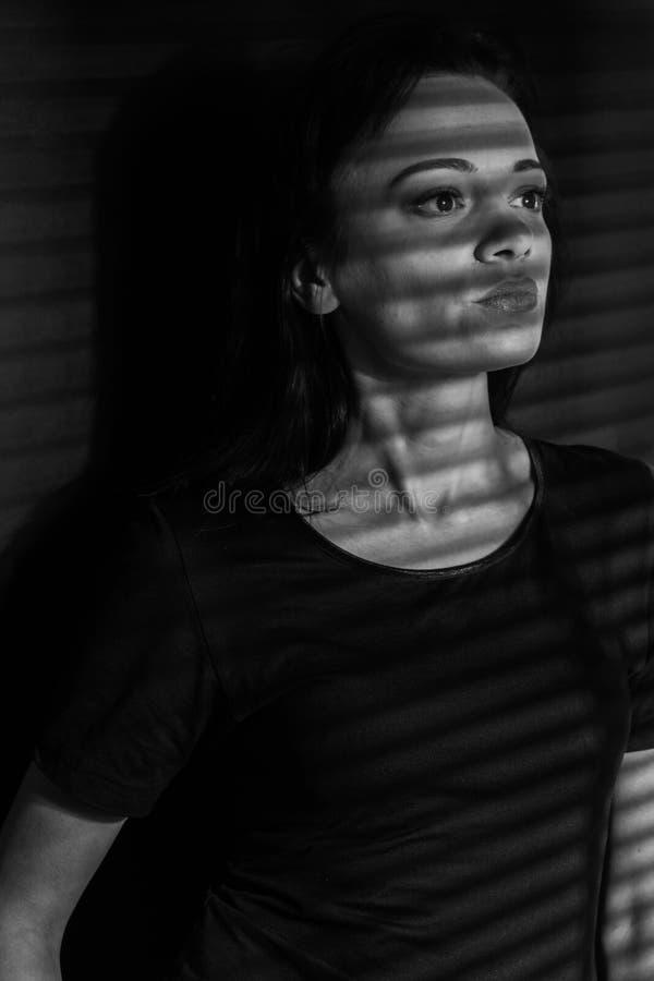 Foto in bianco e nero della ragazza Bianco nero supporto nella tonalità del gioco leggero la ragazza ai ciechi di finestra fotografia stock