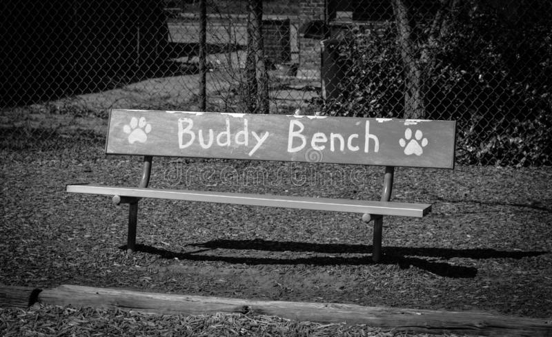 Foto blanco y negro de Buddy Bench en una escuela primaria foto de archivo libre de regalías