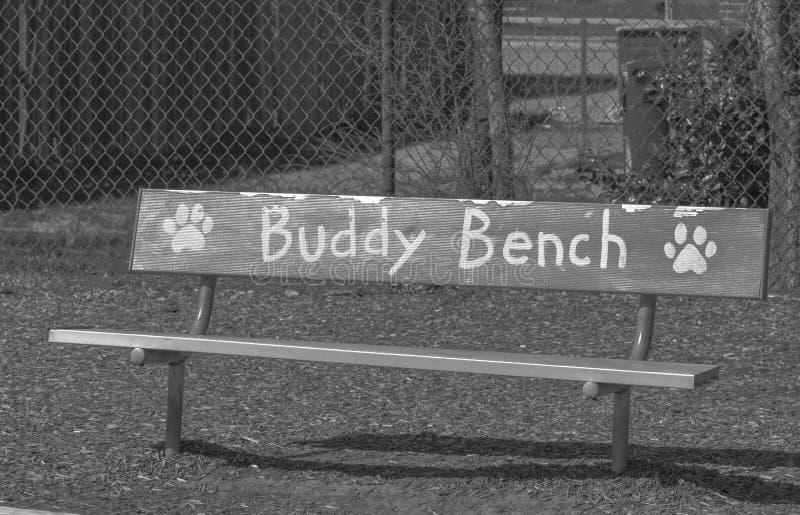 Foto blanco y negro de Buddy Bench en una escuela primaria foto de archivo