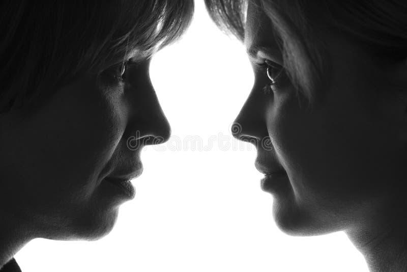 Foto blanco y negro de la madre y de la hija delante de la gente el uno al otro fotos de archivo libres de regalías