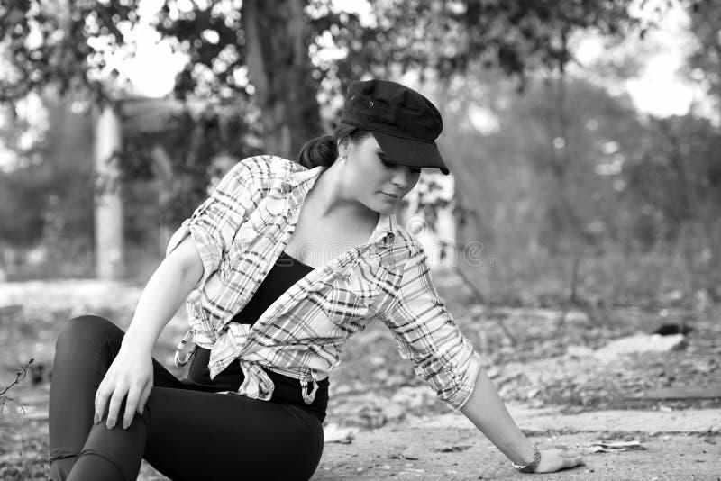 Foto blanco y negro de la muchacha que se sienta con una camisa colorida, polainas y un casquillo imagenes de archivo