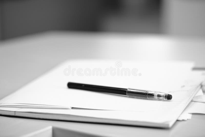 Foto blanco y negro de la pluma y documento sobre un escritorio foto de archivo