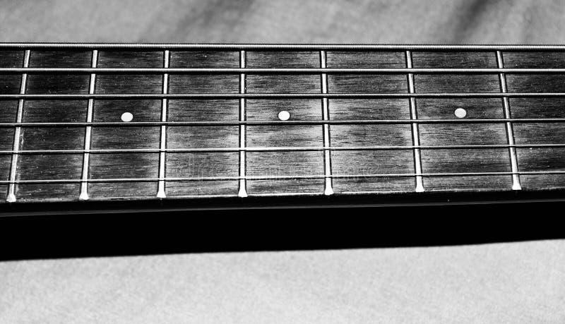 Foto blanco y negro de las secuencias y de los trastes del niño de una guitarra acústica del ` s en el cuello de la guitarra para foto de archivo libre de regalías