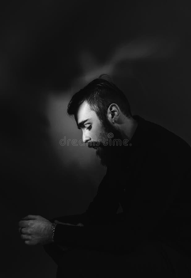 Foto blanco y negro de un hombre con una barba y un peinado elegante vestidos en la camisa negra que se sienta en el taburete en fotos de archivo