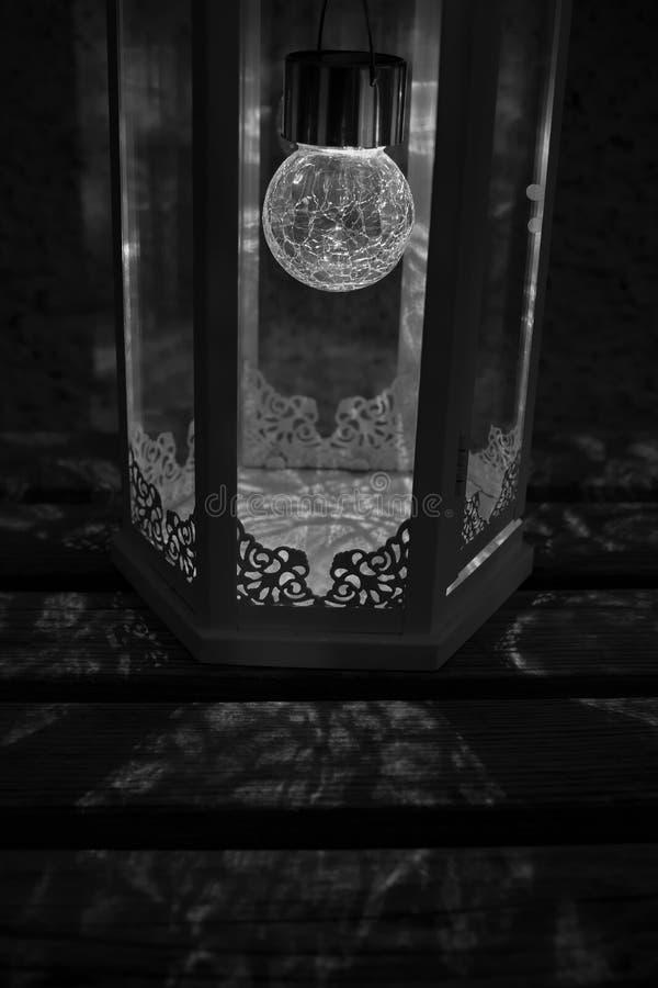 Foto blanco y negro de una linterna iluminada que lanza sombras florales hermosas en un banco de madera imágenes de archivo libres de regalías