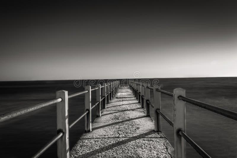 Foto blanco y negro del embarcadero en la puesta del sol imágenes de archivo libres de regalías