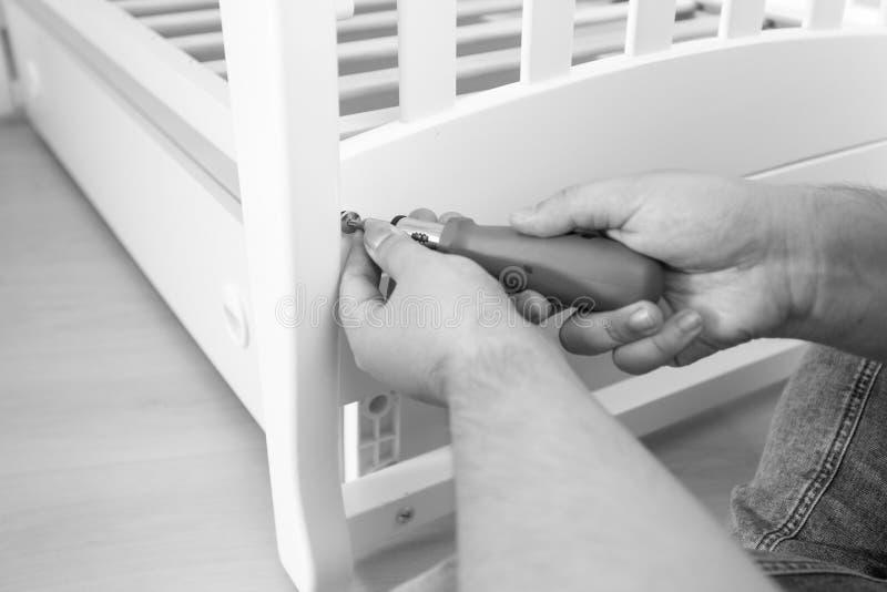 Foto blanco y negro del primer del hombre que aprieta los tornillos en fu fotos de archivo libres de regalías
