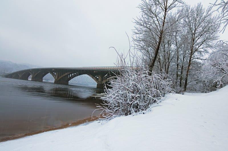 Foto bonita da paisagem do inverno Ponte de Metrosubway refletida no rio de Dnipro Refeições matinais e terra do ` s da árvore da foto de stock royalty free