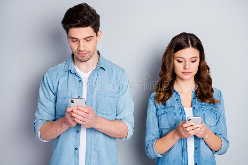 Foto bonita dama bonitinha descuidado casal olhar tela telefônica ignorando usuários viciados usando casual imagem de stock royalty free