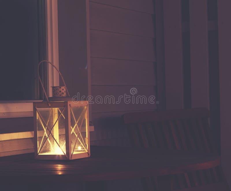 Foto bonita do específico do verão Lanterna com vela ardente fora em uma noite do verão Janela da casa no fundo S bonito imagem de stock