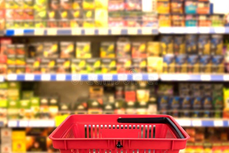 Foto borrada abstrata da loja com a cesta no fundo do bokeh do armazém Conceito do negócio imagem de stock royalty free