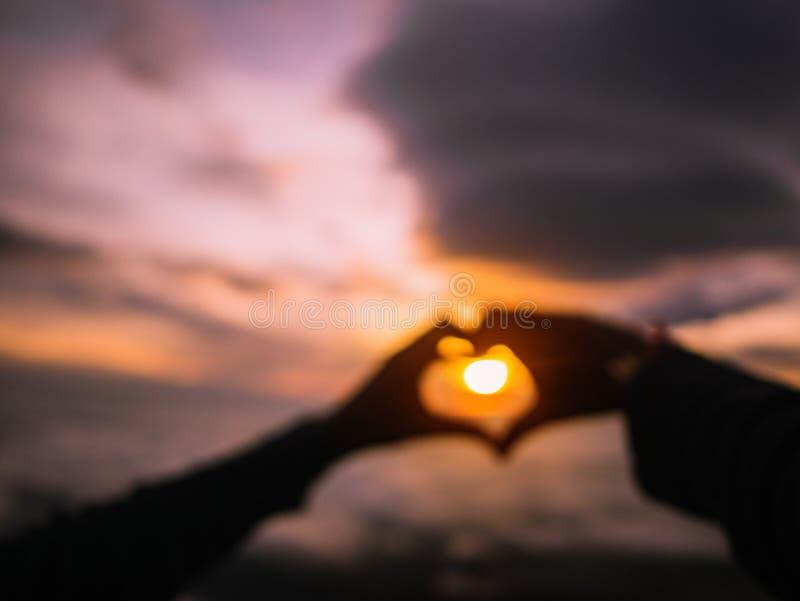 Foto borrada abstrata do sinal da mão do coração da silhueta com nascer do sol fotografia de stock royalty free