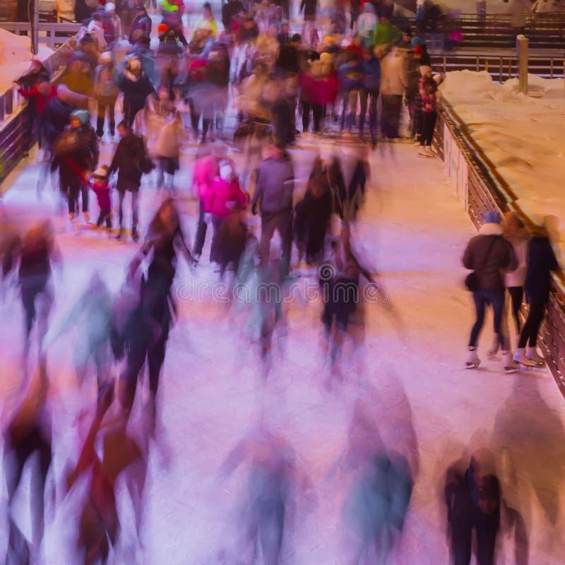 A foto borrada de muitos povos que patinam na pista de gelo na noite cronometra fora no parque no inverno Natal, esporte imagens de stock