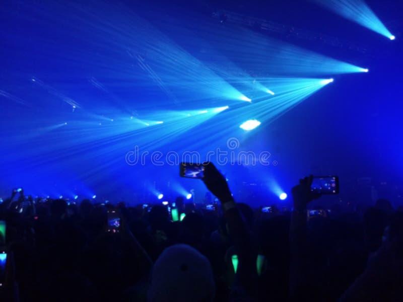 Foto borrada dos povos que usam um telefone esperto para tomar uma foto do festival e das luzes de música que fluem para baixo, c imagens de stock royalty free
