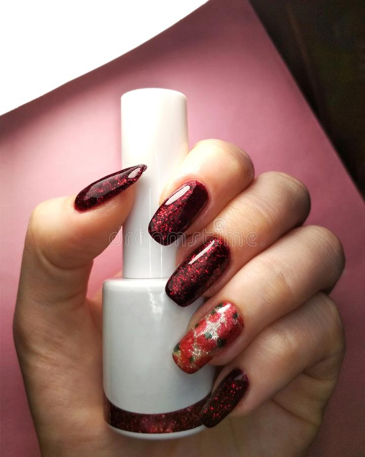 Foto branca da forma da beleza da garrafa do preto do dedo da mão da mulher e do projeto vermelho da amostra de folha do verniz p imagem de stock