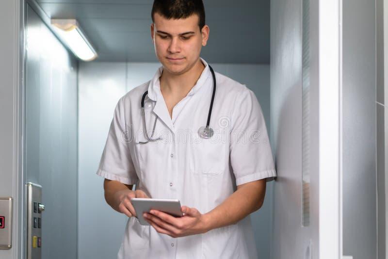 Foto brilhante do doutor masculino no uniforme com o estetoscópio que sai do elevador e que usa a tabuleta do computador no hospi fotos de stock royalty free