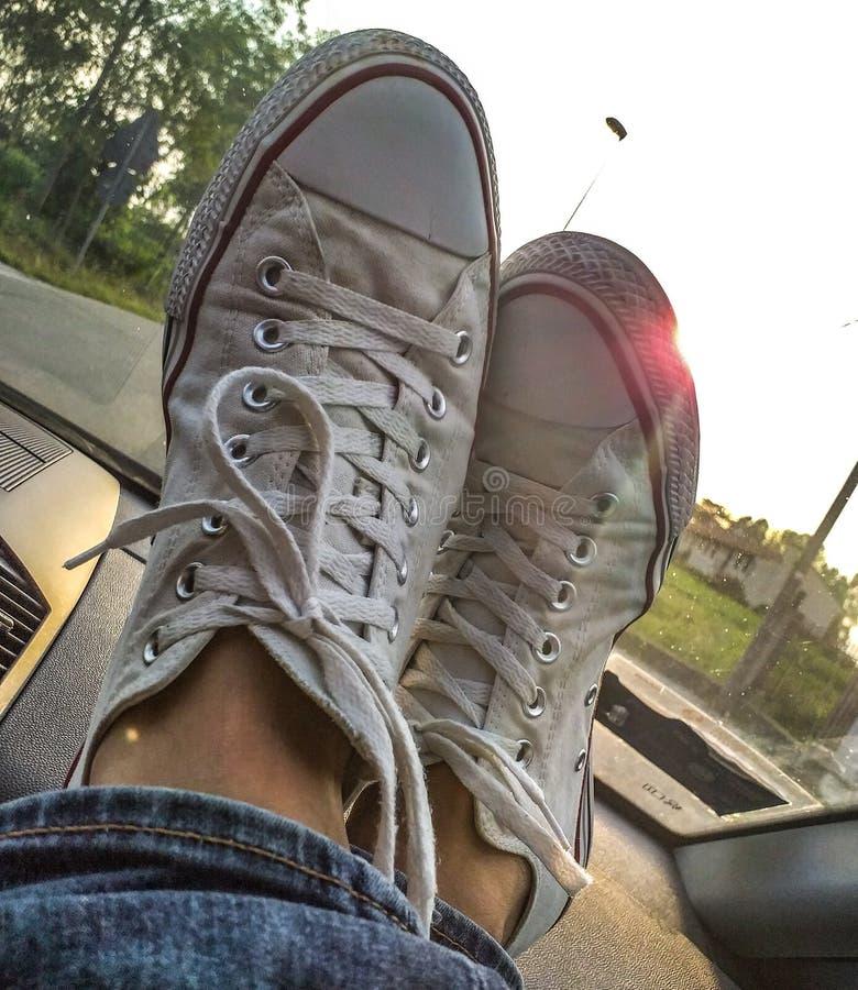 Foto che descrive le scarpe di tennis che riposano su un cruscotto dell'automobile fotografia stock libera da diritti