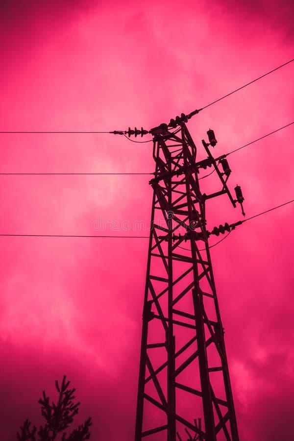 Foto che descrive una vecchia torre potente ad alta tensione di elettricità fotografia stock