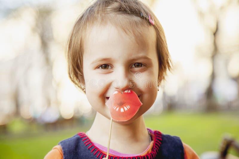 Foto chistosa Labios falsos sin cirugía Muchacha linda divertida del pequeño niño que celebra sonrisa de papel falsa delante de l imagen de archivo