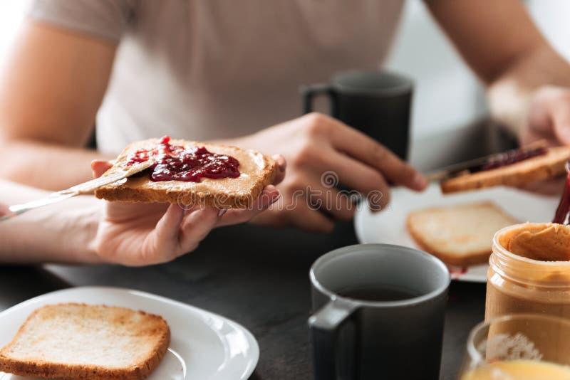 A foto colhida da mulher pôs o doce sobre o pão fotos de stock