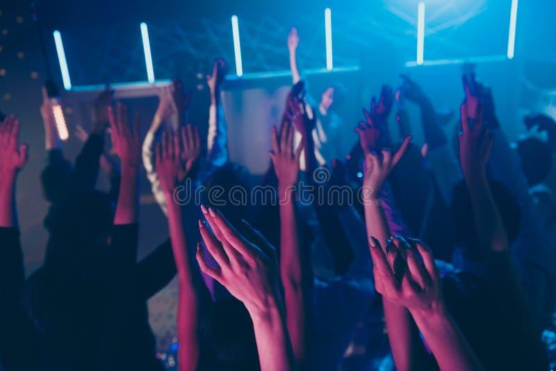 A foto colhida da vista borrada das grandes mãos do aumento dos povos do grupo aprecia o salão de baile da discoteca do disco fotos de stock