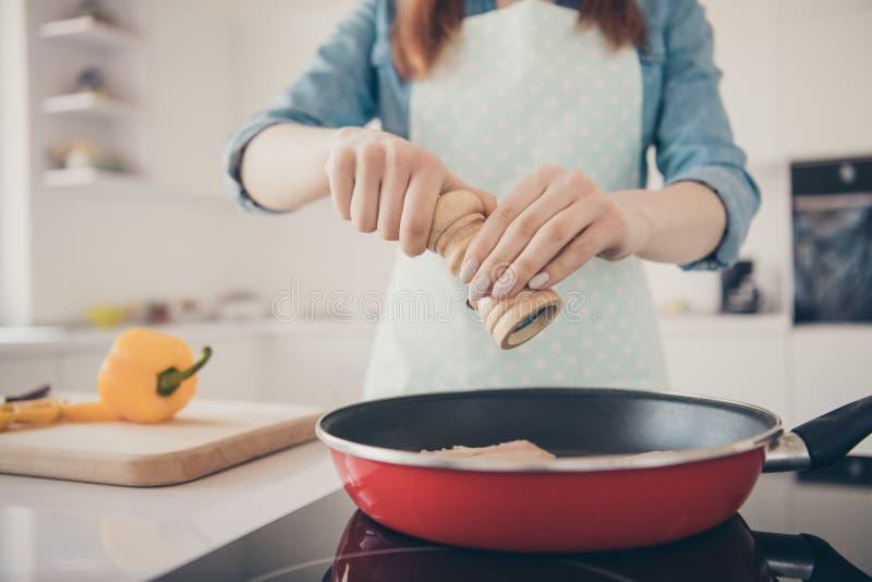 A foto colhida do close up da esposa pura dos braços pôs especiarias diferentes no avental pontilhado do prato desgaste saboroso foto de stock