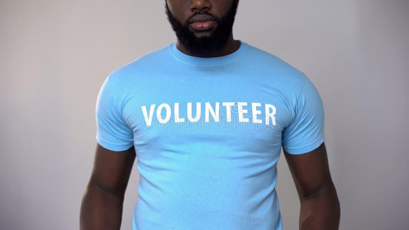 Foto colhida do voluntário masculino preto no t-shirt azul, os sem-abrigo de ajuda fotos de stock royalty free