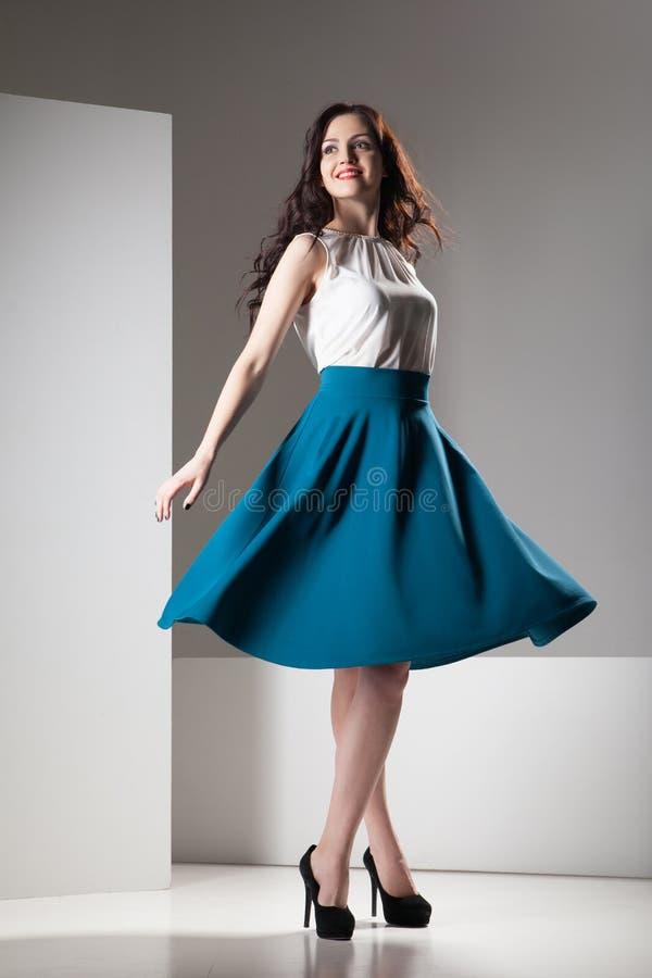 Foto colorida de uma mulher na parte superior e na obscuridade brancas - saia azul imagens de stock royalty free