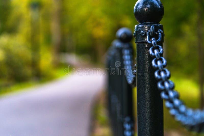 Foto colorida del camino en un parque, entre el bosque - opinión del primer de la cerca de cadena con el fondo borroso con el esp fotos de archivo libres de regalías