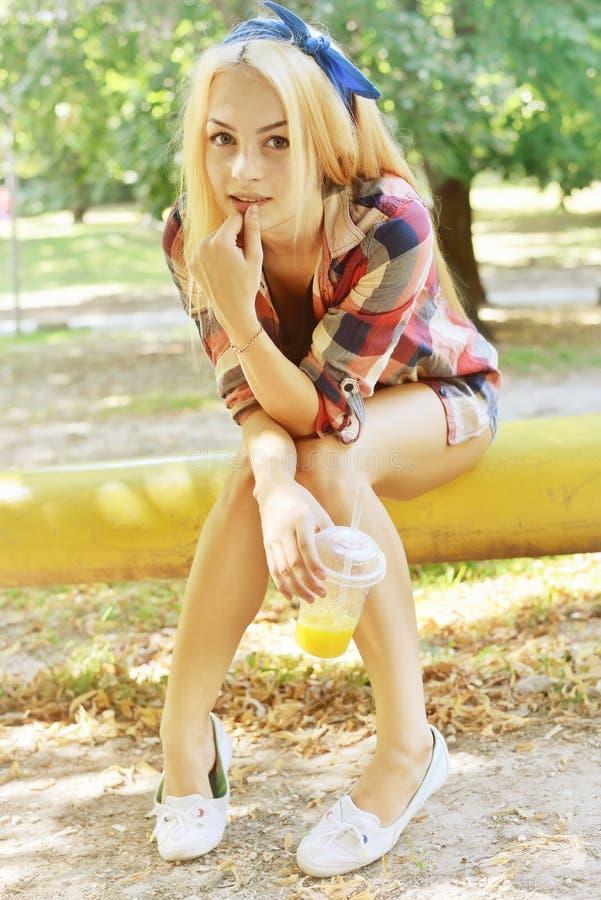 Foto colorida exterior do close up do verão da menina de sorriso feliz loura bonita nova com o coctail à disposição que tem o div foto de stock royalty free