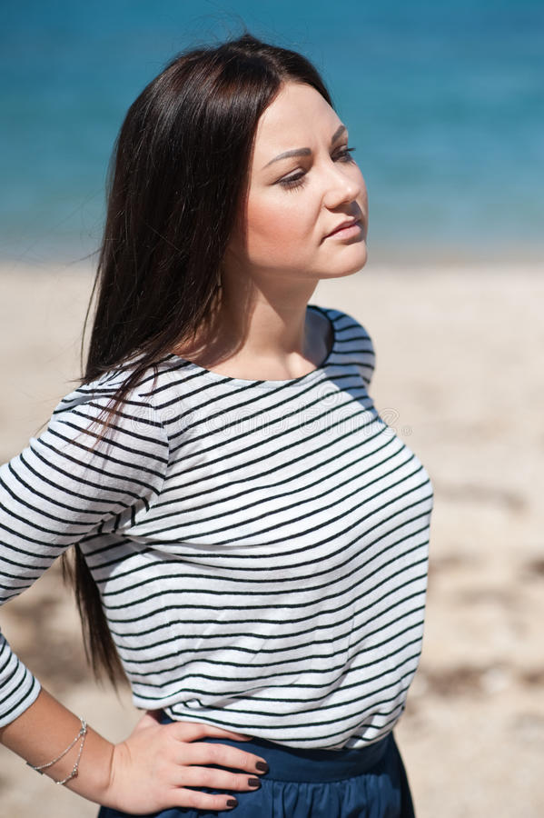 Foto común de la mujer triguena alta hermosa en la playa en foto de archivo libre de regalías