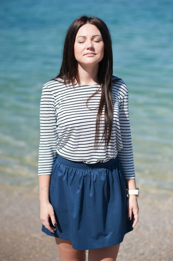 Foto común de la mujer triguena alta hermosa en la playa en foto de archivo