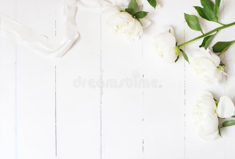 Foto común diseñada Composición de tabla femenina de la boda con la cinta blanca del flor de las peonías y de seda en de madera b foto de archivo libre de regalías