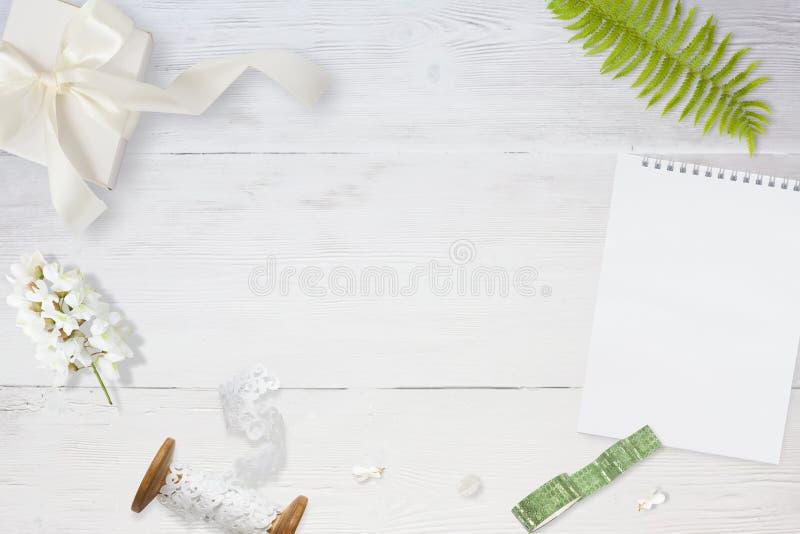 Foto común diseñada Maqueta femenina de la mesa de la boda Tarjeta de felicitación Flores, papel, pluma, cinta en blanco delicado fotos de archivo