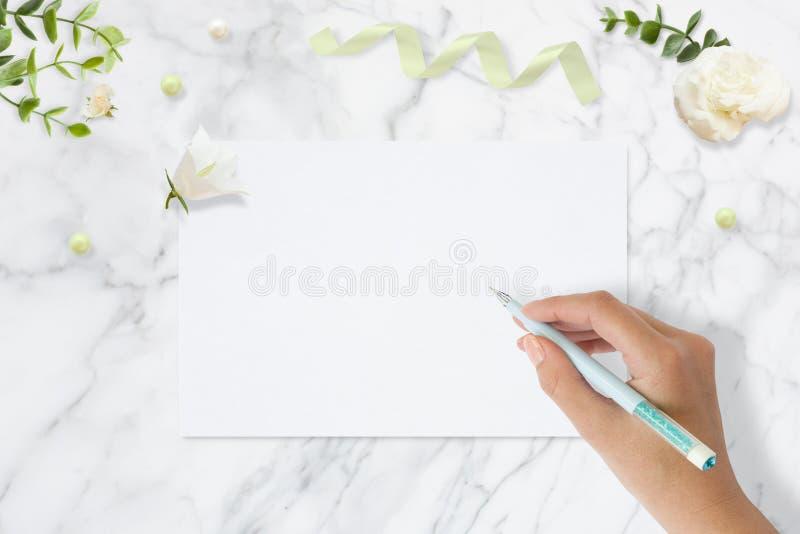 Foto común diseñada Maqueta femenina de la mesa de la boda Tarjeta de felicitación Flores, papel, pluma, cinta en el mármol delic fotografía de archivo