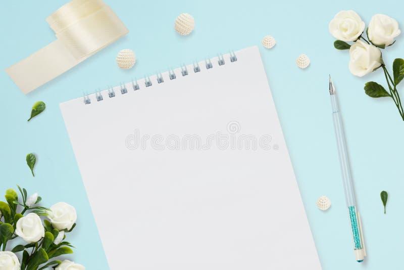 Foto común diseñada Maqueta femenina de la mesa de la boda Tarjeta de felicitación Rosas blancas, cuaderno, pluma, cinta en azul  fotografía de archivo