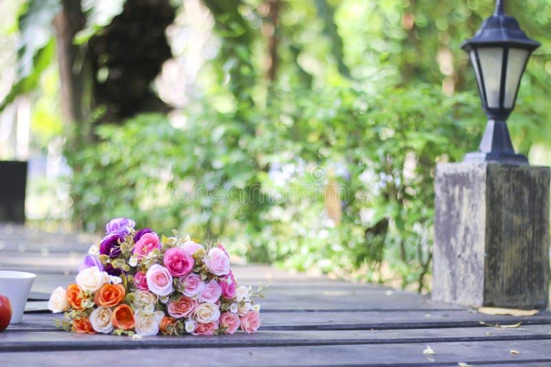 Foto común: Florece el ramo, los libros y la taza en la tabla de madera en a foto de archivo