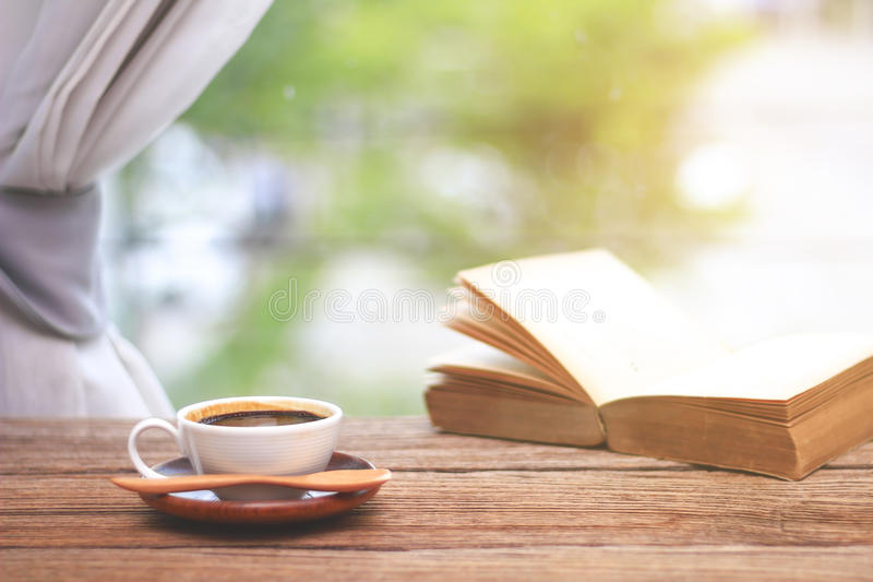 Foto común - taza de café con los libros por mañana en la ventana imagen de archivo libre de regalías