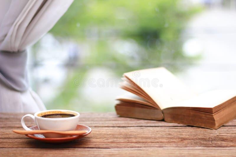 Foto común - taza de café con los libros por mañana en la ventana imagen de archivo