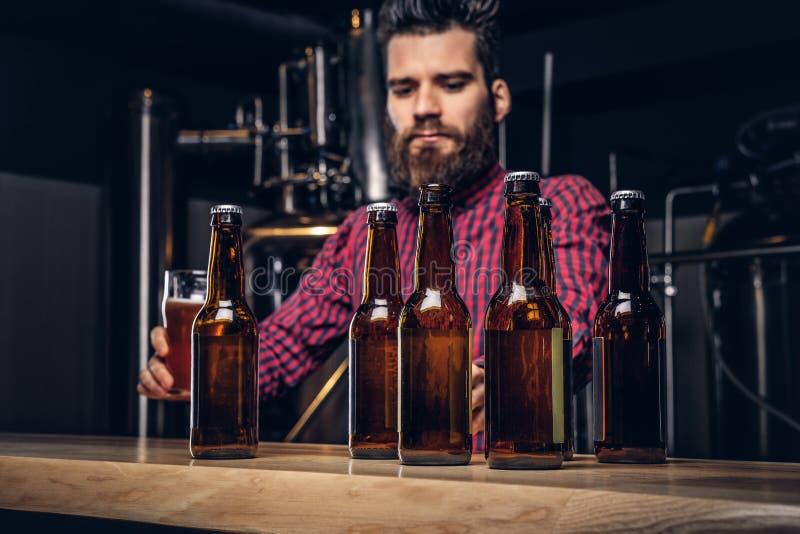 Foto com as garrafas de cerveja do ofício no primeiro plano e no homem farpado que bebem no fundo foto de stock royalty free