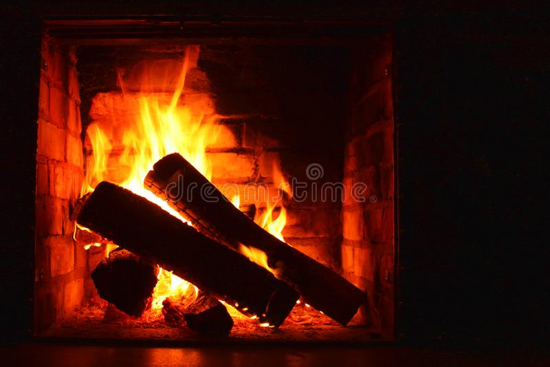 Foto com a chaminé bonita do tijolo com a lenha que queima-se no fogo e com lugar para a inscrição de cumprimento na obscuridade imagens de stock royalty free