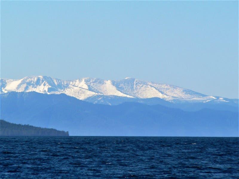 Foto com o fundo de águas azuis do Lago Baikal em Rússia, e os picos de montanha no horizonte imagem de stock